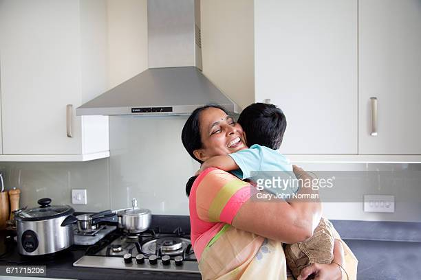 Happy Grandmother hugging young grandson at home
