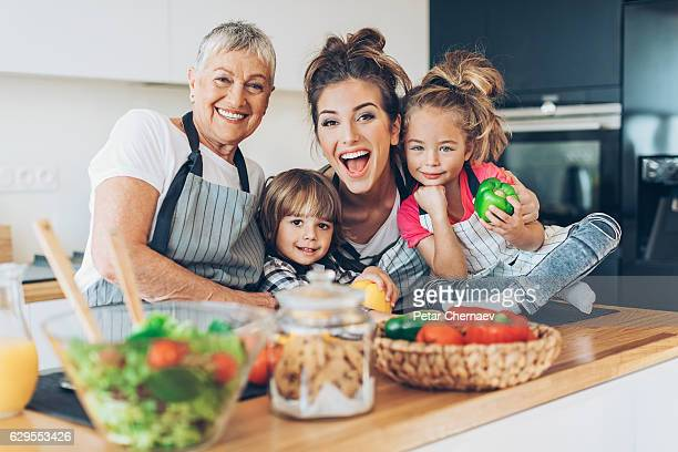 Happy grandmother, mother and two children in the kitchen
