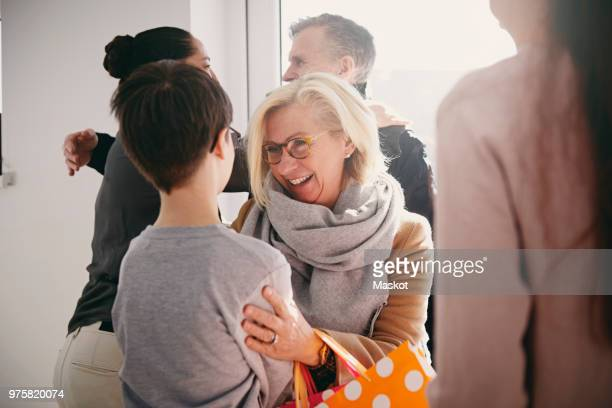 happy grandmother talking to grandson while senior father embracing daughter at home - ankunft stock-fotos und bilder
