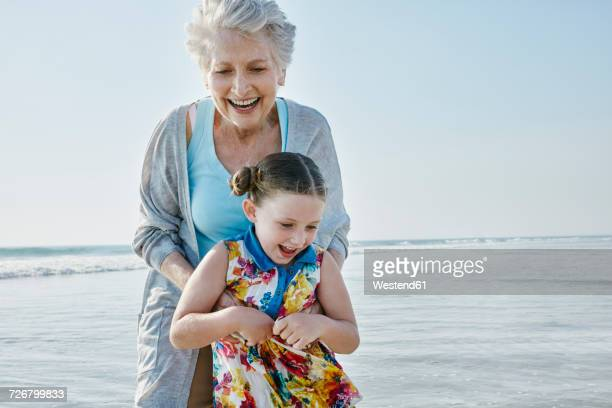 happy grandmother with granddaughter on the beach - beautiful grandmothers stock pictures, royalty-free photos & images