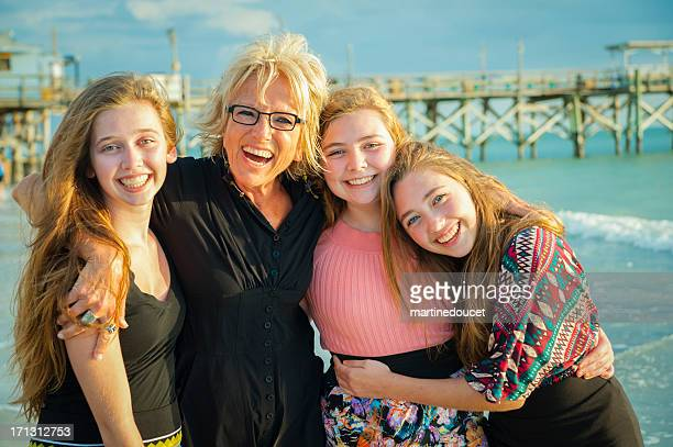 Happy grandmother with her three lovely grandaugthers on the beach.