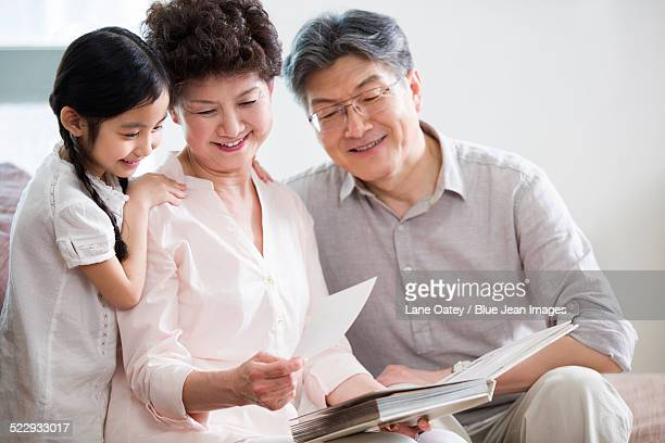 happy grandparents and granddaughter looking at photo album - asian granny pics stock photos and pictures