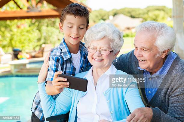 Happy grandparents and grandson take selfie with smartphone