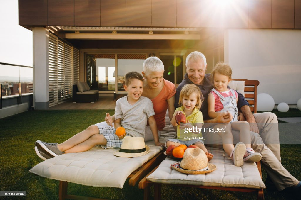 Happy grandparents and their three grandchildren enjoying a day on a terrace. : Stock Photo