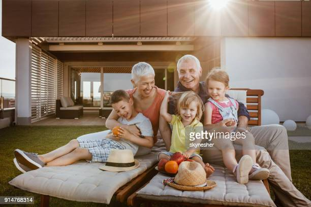 happy grandparents and their three grandchildren enjoying a day on a terrace. - penthouse girls stock pictures, royalty-free photos & images