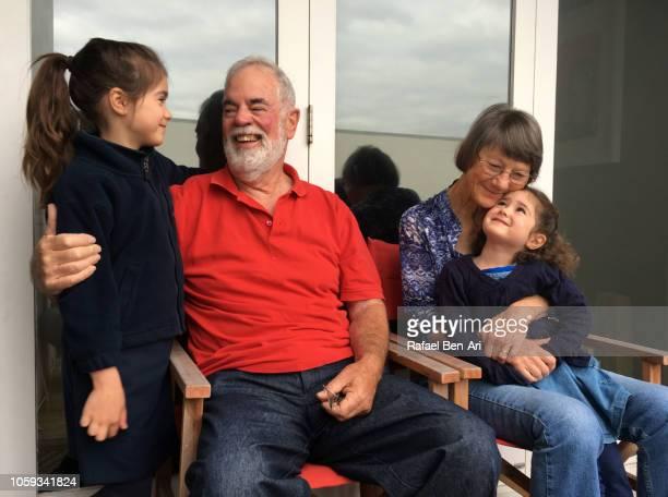 happy grandparents couple embarrassing their granddaughters - rafael ben ari stock-fotos und bilder