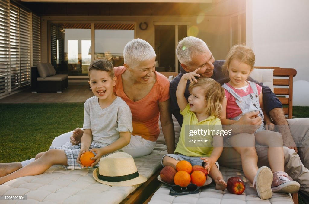 Happy grandparents enjoying while relaxing with their small grandkids on deck chairs. : Stock Photo