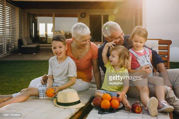 happy grandparents enjoying while relaxing with their small grandkids on deck chairs. - penthouse girls stock pictures, royalty-free photos & images