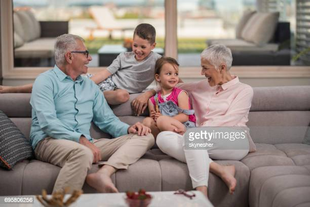 happy grandparents enjoying with their grandkids while relaxing on the sofa. - penthouse girls stock photos and pictures