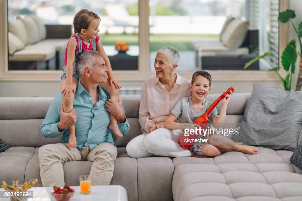 happy grandparents having fun with their small grandkids at home. - penthouse girls stock pictures, royalty-free photos & images