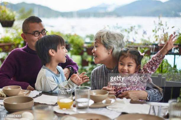 happy grandparents playing with children at table - cinese foto e immagini stock