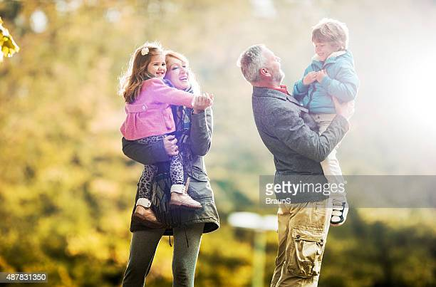 Happy grandparents playing with their grandchildren in nature.