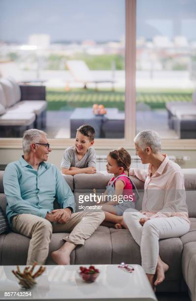 happy grandparents talking to their grandchildren on sofa at home. - penthouse girls stock pictures, royalty-free photos & images