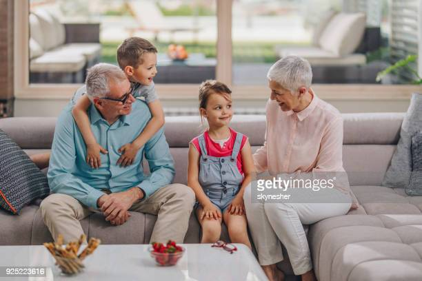 happy grandparents talking to their grandkids in the living room. - penthouse girls stock pictures, royalty-free photos & images