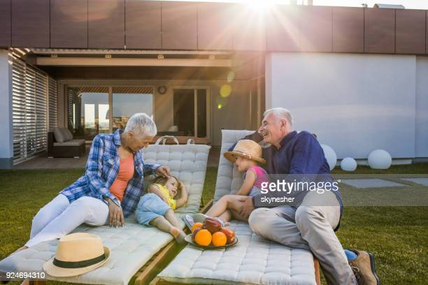 happy grandparents talking to their grandkids while relaxing on deck chairs. - penthouse girls stock pictures, royalty-free photos & images
