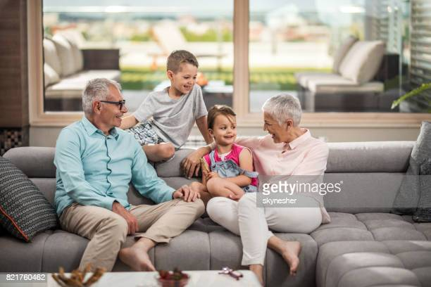 happy grandparents talking to their small grandkids in the living room. - penthouse girls stock pictures, royalty-free photos & images