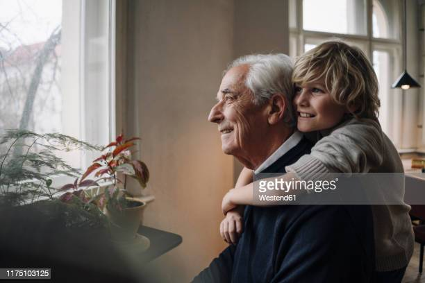 happy grandson embracing grandfather at home - grandson stock pictures, royalty-free photos & images