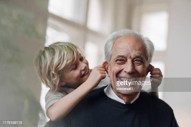 happy grandson pulling grandfather's ears at home - day 2 stock-fotos und bilder