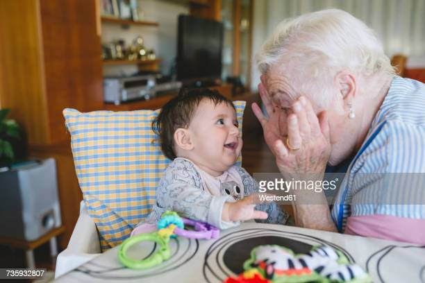 Happy great-grandmother playing with a baby girl sitting in the high chair next to the table with toys