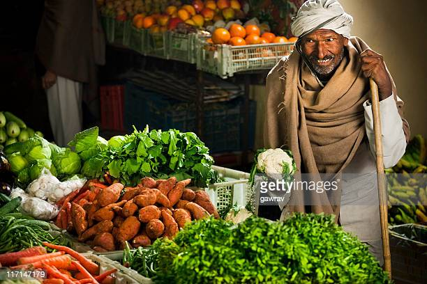 Happy greengrocer selling vegetables and fruits at his shop.