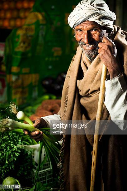 Happy greengrocer selling vegetables and fruits at his shop