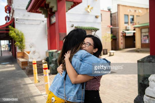 happy greetings of young women in chinatown - perth australia stock photos and pictures