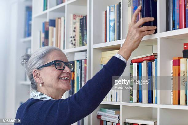 Happy grey haired mature woman selecting book from bookshelves