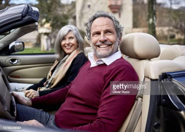 happy grey-haired couple in convertible car - prosperity stockfoto's en -beelden