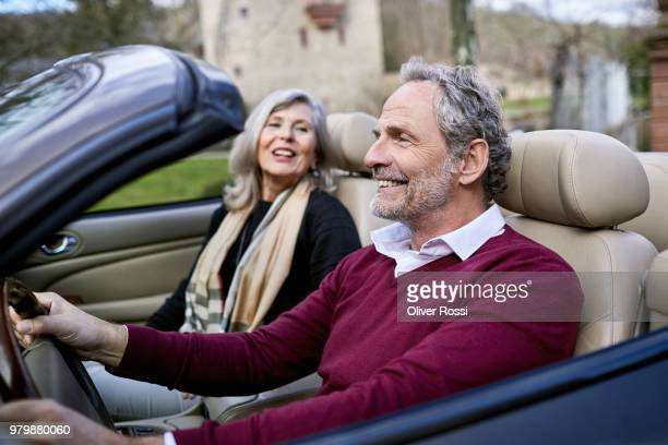 happy grey-haired couple in convertible car - prosperity stock pictures, royalty-free photos & images