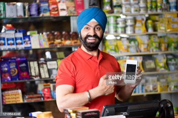 happy grocery store owner holding credit card reader - indian ethnicity stock pictures, royalty-free photos & images