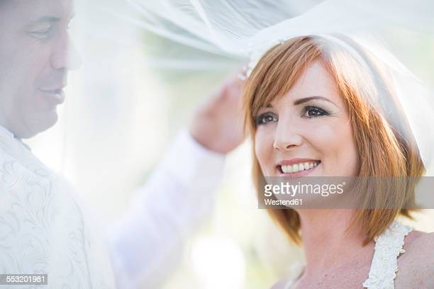 Happy groom and bride covered with veil ready for her wedding