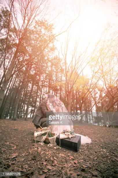 happy groom kissing on bride's forehead in forest - blindfolded bride stock pictures, royalty-free photos & images