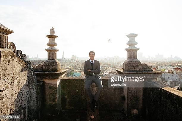 Happy groom sitting on a rooftop in Havana Cuba