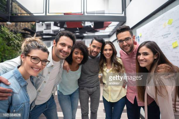 Happy group of business people taking a picture at a creative office