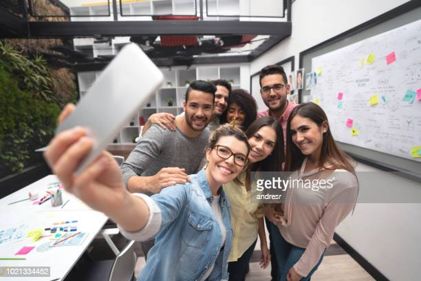 Happy group of business people taking a selfie at a creative office