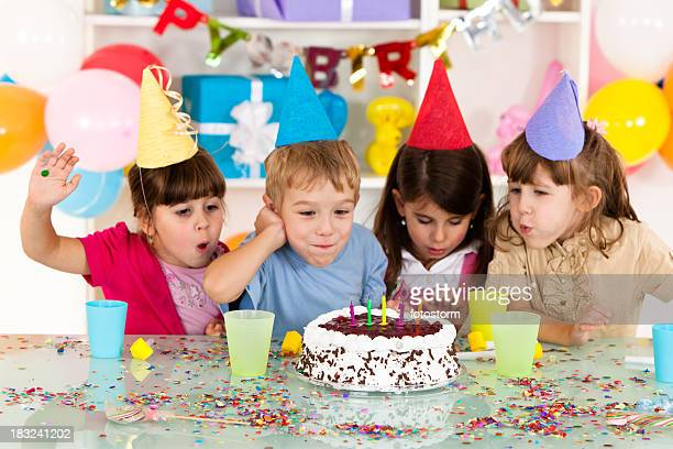 Happy group of children blowing candles on birthday cake
