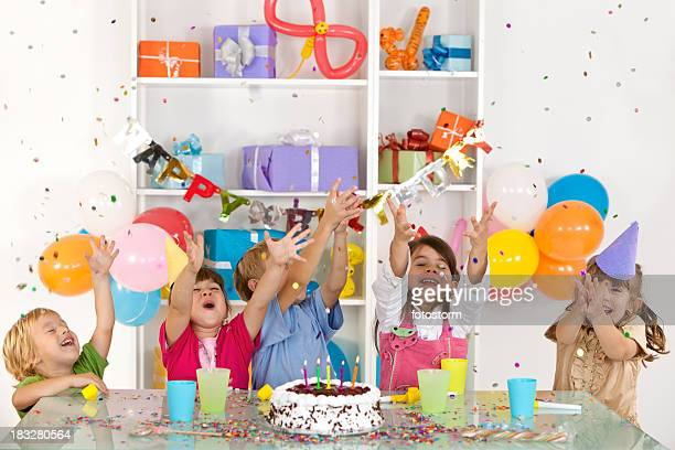 happy group of children catching confetti at birthday party - birthday balloons stock photos and pictures