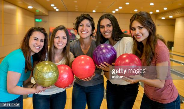 Happy group of female friends having fun bowling looking at camera smiling