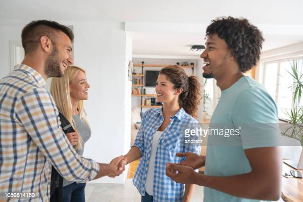 Happy group of flat mates greeting each other at home