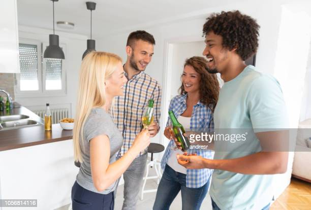 Happy group of flat mates having drinks at home