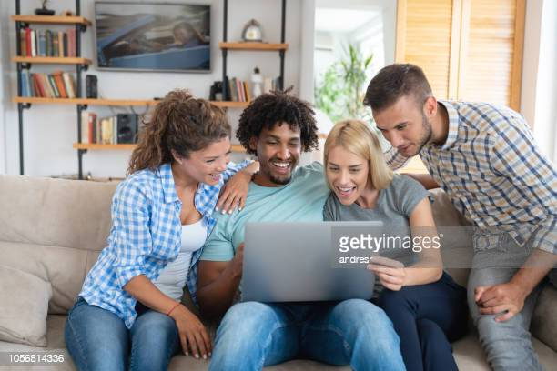 Happy group of flat mates looking at social media at home