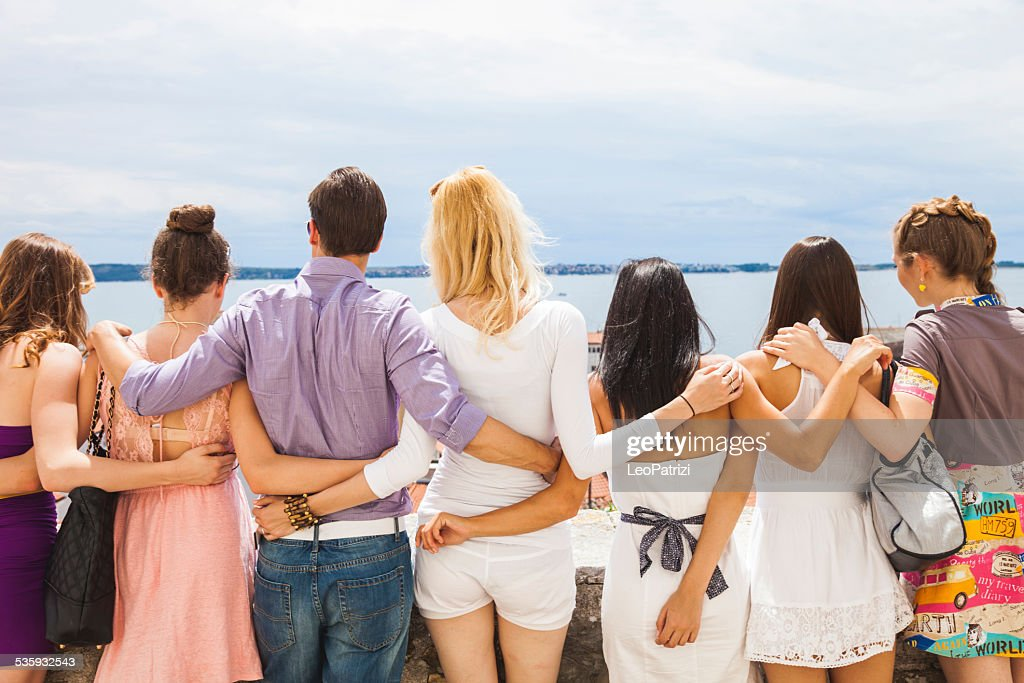 Happy group of friends embracing and looking at view : Stock Photo