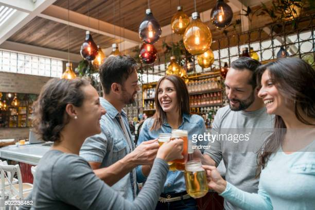 Happy group of friends having drinks at a restaurant
