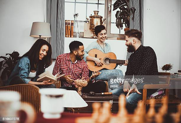 Happy group of friends  singing  and  playing music  together