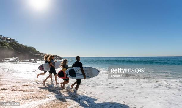 Happy group of friends surfing at the beach
