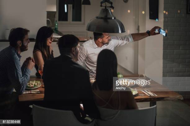 Happy group of friends taking selfie during dinner party.