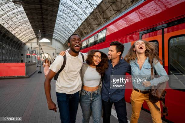 happy group of friends traveling by train - railroad station stock pictures, royalty-free photos & images