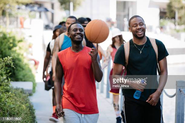Happy group of friends walking and talking and spinning a basketball