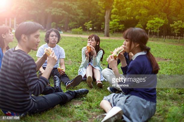 Happy group of Japanese friends eat in the park, Tokyo