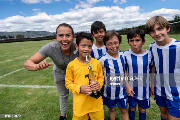 feliz grupo de crianças, ganhando um troféu de futebol - trophy - fotografias e filmes do acervo